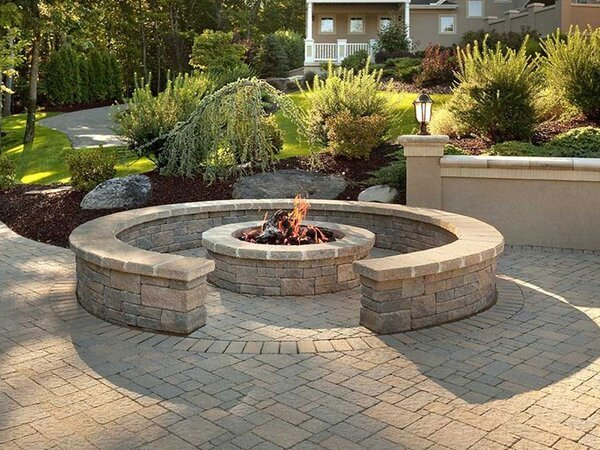 Patio with fire pit that has a sitting wall around it