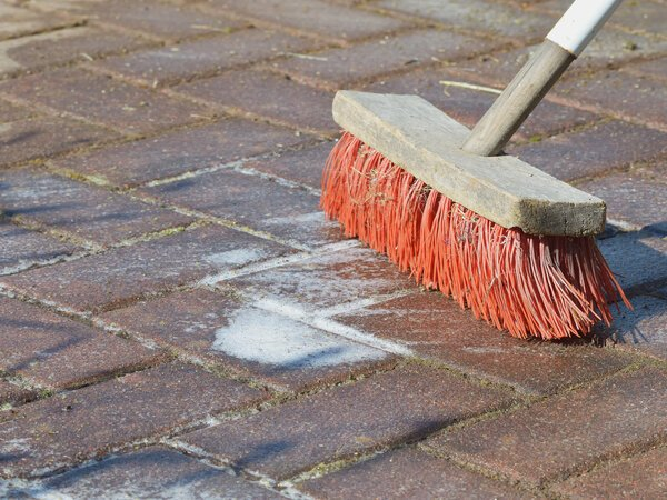How to clean a patio using a scrubbing brush and cleanser